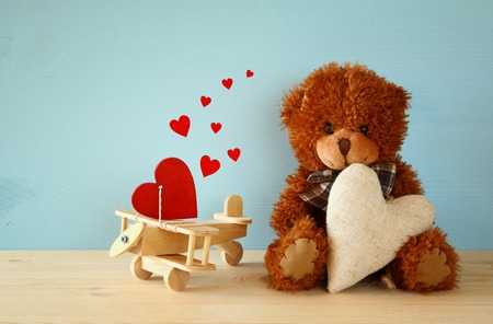 sweet heart: Cute teddy bear sitting and holding a heart, on wooden table Stock Photo