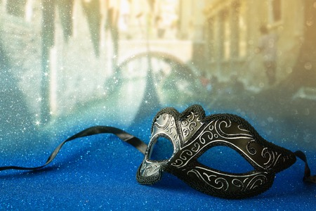 Image of elegant venetian mask in front of blurry Venice background. Glitter overlay
