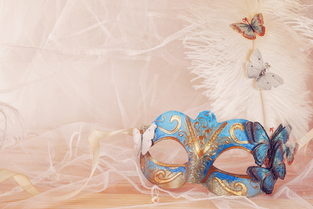 tulle: Image of delicate blue elegant venetian mask next to pearls in front of white tulle background. Filtered photo