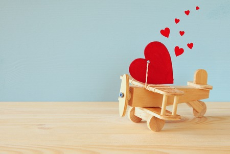 wooden toy: Valentines day background. Wooden plane with heart on the table