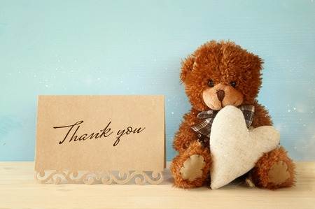 Cute teddy bear sitting and holding a heart next to thank you card, on wooden table