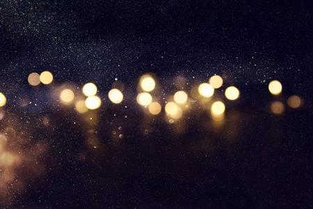glitter vintage lights background. gold and black. de-focused