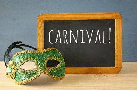 Image of green elegant venetian mask next to empty blackboard
