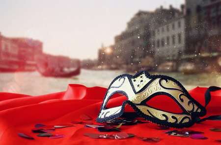 Image of elegant venetian mask on red silk fabric in front of blurry Venice background. Glitter overlay Stock Photo
