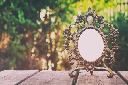 Image of vintage antique classical frame on wooden table outdoors at afternoon. selective focus. Filtered image Stock Photo