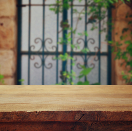 empty table: Empty table in front of blurry antique wooden door. Ready for product display montage Stock Photo
