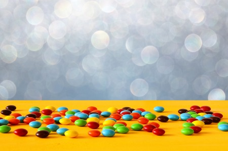 Party table with candies in front of glitter background.