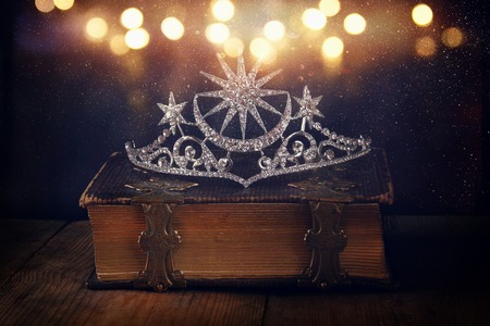 low key image of beautiful diamond queen crown on old book. vintage filtered with glitter overlay. selective focus. medieval period concept