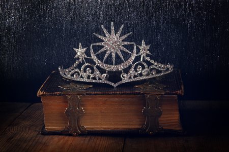 selective focus: low key image of beautiful diamond queen crown on old book. vintage filtered with glitter overlay. selective focus. medieval period concept