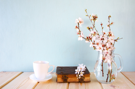 old book, cup of coffee next to spring white flowers on wooden table Stock Photo