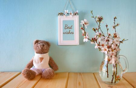 photo frame: cute teddy bear sitting next to spring white cherry blossoms tree Stock Photo