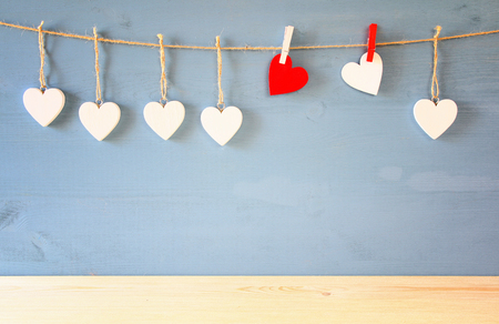 Valentines day background. hearts hanging in front of blue background. With wooden floor. product display backdrop Stock Photo