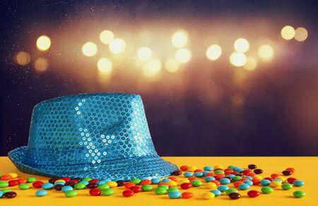 Blauwe glanzende feesthoed naast kleurrijke snoepjes op gele houten tafel