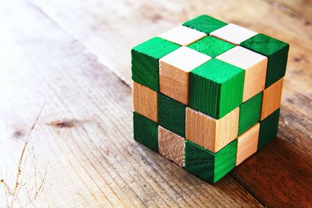 square image: image of square wooden cube puzzle, over wooden table. Stock Photo