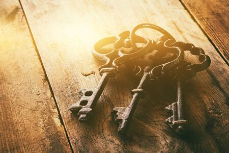 old wallpaper: close up image of vintage skeleton keys over wooden table and bright light as reveletaion concept