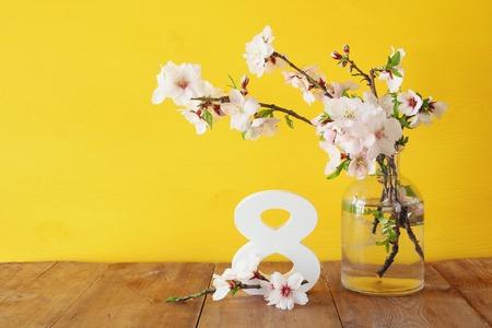 Internationaal vrouwendagconcept. Kersenboomtakken in de vaas en de datum op houten tafel