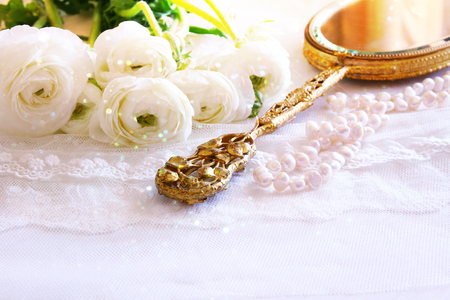 neckless: Background of white delicate lace fabric, hand mirror and white flowers