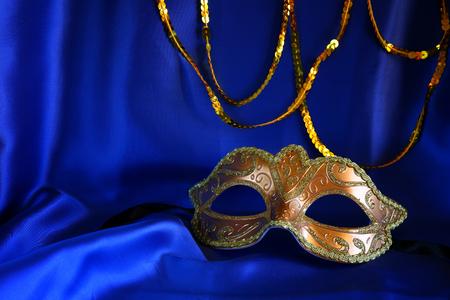 mardigras: Image of elegant gold venetian mask on blue silk background