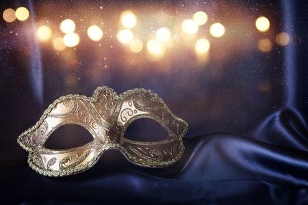 Imagen de la elegante máscara veneciana de oro sobre fondo azul de seda