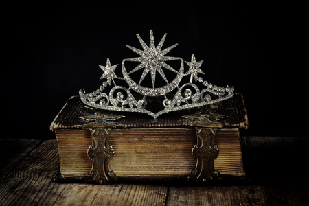 low key image of beautiful diamond queen crown on old book. vintage filtered. selective focus. medieval period concept