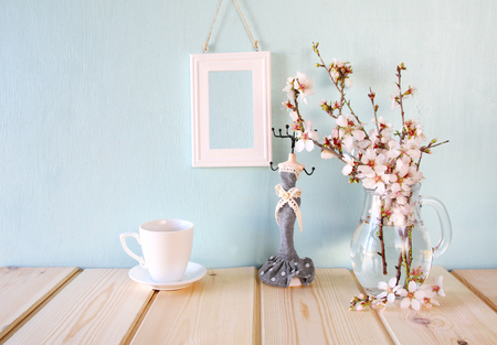 room decor: vintage jewelery stand with pearls necklace, blank frame next to white spring flowers on wooden table