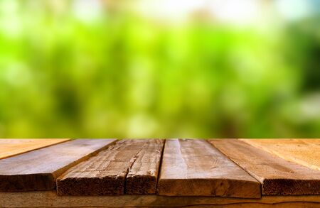 Empty rustic table in front of spring abstract bokeh background. product display and picnic concept