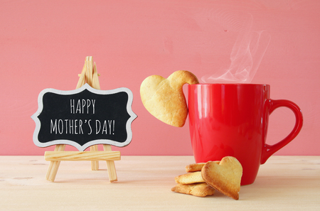 mothers day concept image. Board next to cup of coffee and heart cookies 版權商用圖片