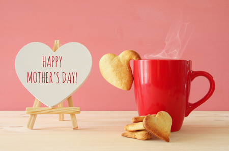 mothers day concept image. Board next to cup of coffee and heart cookies Stok Fotoğraf