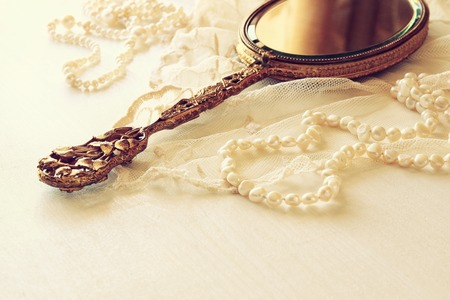 neckless: Background of white delicate lace fabric and hand mirror Stock Photo