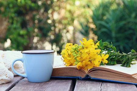old book, cup of coffee next to field flowers on wooden table outdoors at afternoon. selective focus Stock Photo