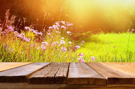 Vaciar la mesa rústica delante de flores de campo hermoso de primavera. Visualización de productos y concepto de picnic