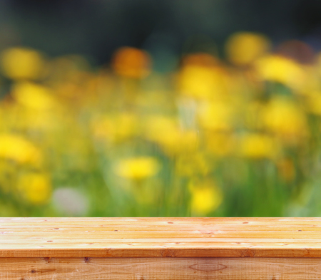Empty rustic table in front of spring beautiful field flowers background. product display and picnic concept