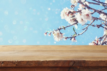 cerezos en flor: wooden rustic table in front of spring white cherry blossoms tree. vintage filtered image. product display and picnic concept