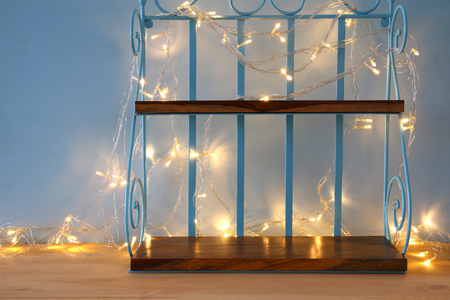 display advertising: Vintage beautiful empty shelf display with gild garland lights for product advertising