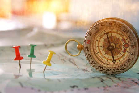 pins attached to map, showing location or travel destination and old compass. selective focus.