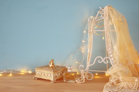 neckless: Background of white delicate lace fabric, perfume and gold garland lights on wooden table