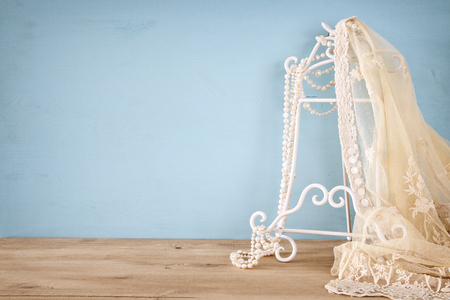 vintage white crochet lace top and pearls in front of blue background