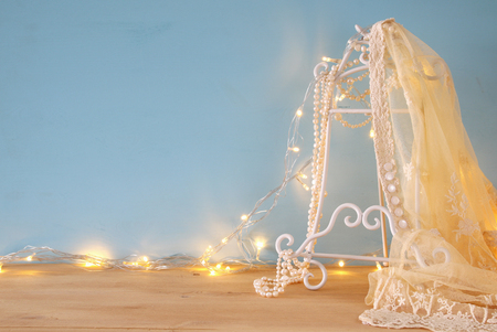 vintage white crochet lace top, pearls and warm garland lights in front of blue background