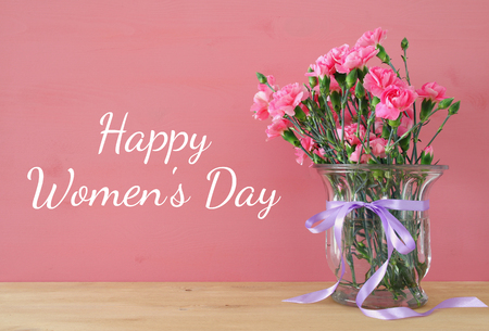 flowers in vase: International women day concept. Bouquet of Carnation flowers in the glass vase on wooden table Stock Photo