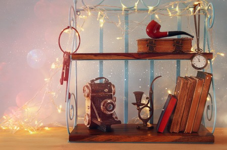 decorative objects: Classical shelf with vintage male objects, decorative old camera and gold garland lights.