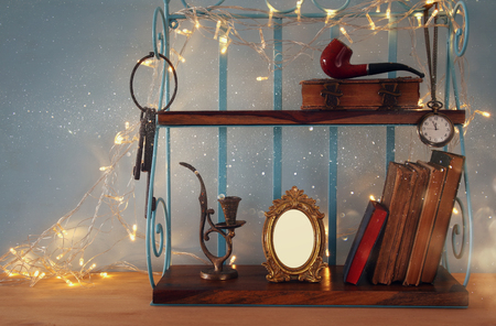 vintage objects: Classical shelf with vintage male objects and blank frame with gold garland lights. Ready to put photography Stock Photo