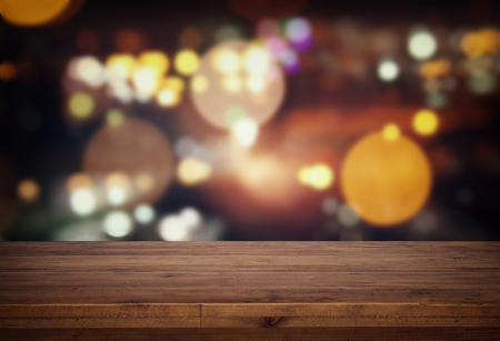 Image of wooden table in front of abstract blurred restaurant lights background Stok Fotoğraf