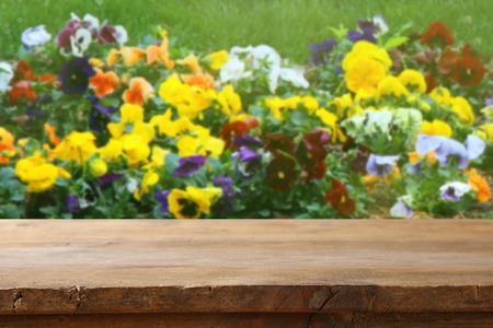 renew.: Empty rustic table in front of spring beautiful field flowers background. product display and picnic concept