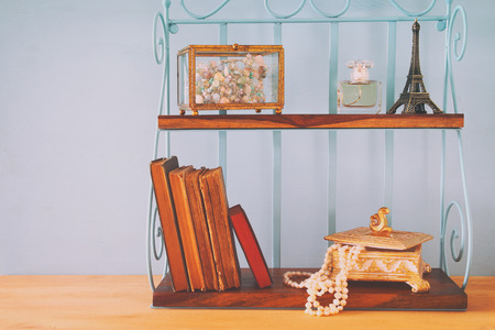 neckless: Classic shelf with vintage objects on wooden table.