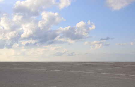 asphalt: image of asphalt road and clear blue sky with clouds at horizon. Stock Photo