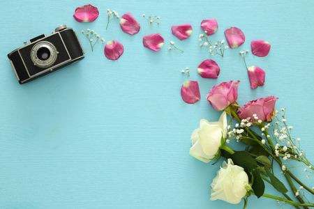 Top view of old camera and roses over wooden table.