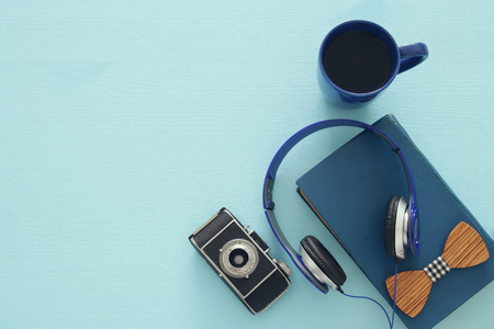 audio book: cup of coffee, old book, vintage photo camera and headphones on blue wooden background. top view image Stock Photo