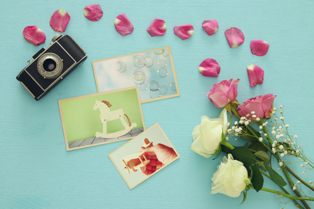 old photograph: Top view of photography collection next to old camera and roses over wooden table. Flat lay