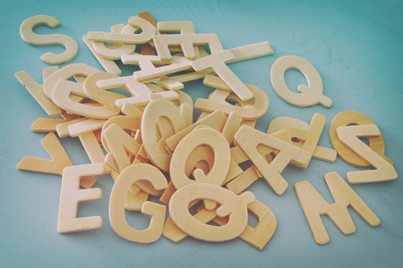 Set of a wooden letters of the English alphabet on wooden blue background. Filtered image 스톡 콘텐츠