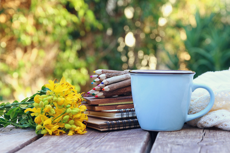 Image of notebooks, colorful pencils next to field flowers on wooden table outdoors at afternoon. selective focus
